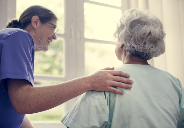 Nurse taking care of an old woman - Stock Photo - Images