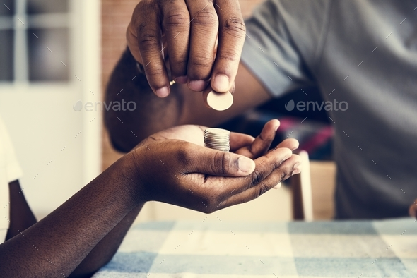 Dad giving coins to his daughter - Stock Photo - Images