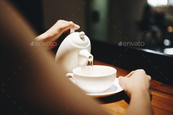 Woman pouring a hot drink - Stock Photo - Images