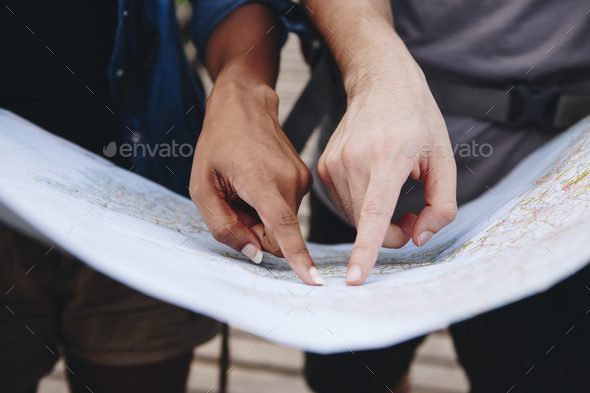 Friends finding directions with a map - Stock Photo - Images