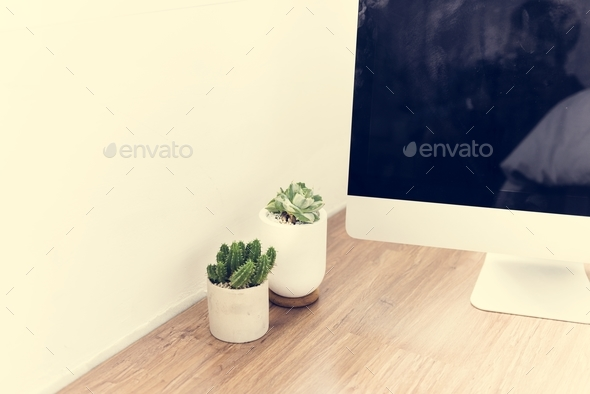 Closeup of computer on wooden table with cactus plant - Stock Photo - Images
