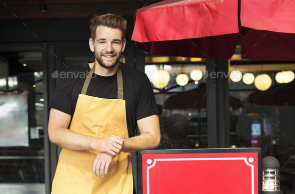 Small business owner standing infront of restaurant - Stock Photo - Images