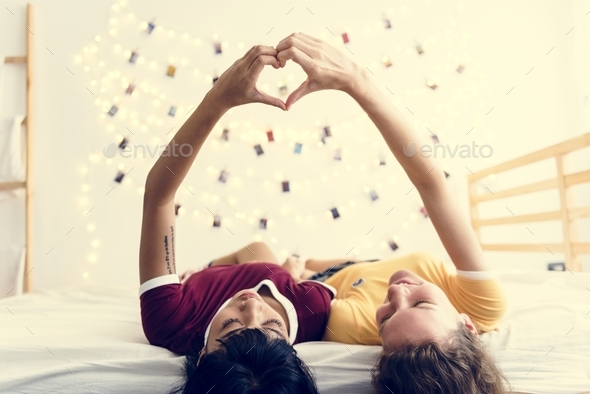 Women lying on the bed together - Stock Photo - Images