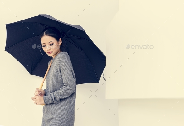 Asian woman holing umbrella on white background - Stock Photo - Images