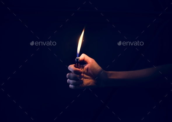 Hand holding lit lighter in the dark - Stock Photo - Images