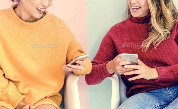 Caucasian and asian women sitting using mobile phones together with pink and mint green background - Stock Photo - Images