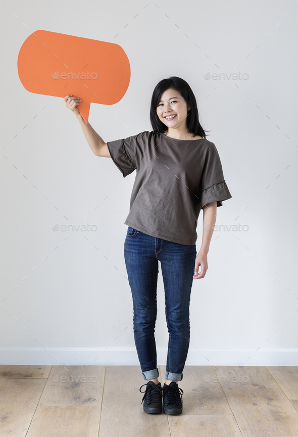 Happy Asian woman holding copyspace speech bubble - Stock Photo - Images