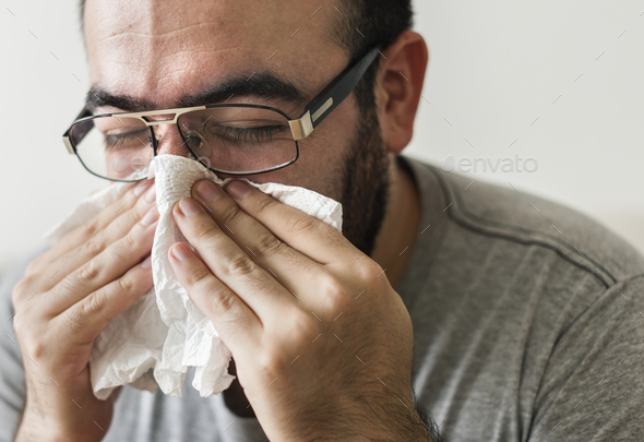 Man sneezing into tissue paper - Stock Photo - Images