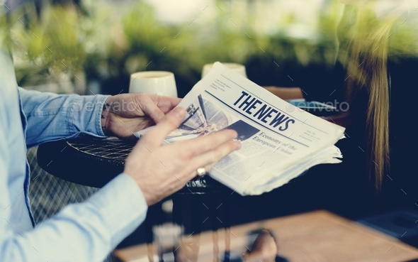 Hands holding a newspaper reading at the cafe - Stock Photo - Images