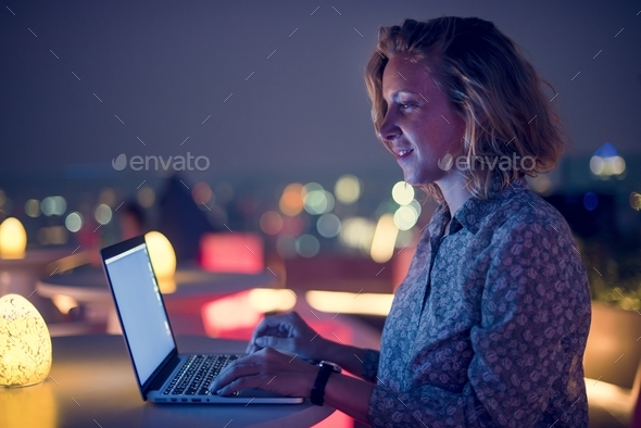 Woman working on a laptop at a rooftop bar - Stock Photo - Images