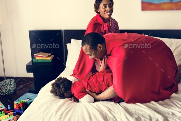 Black family playing together on bed - Stock Photo - Images