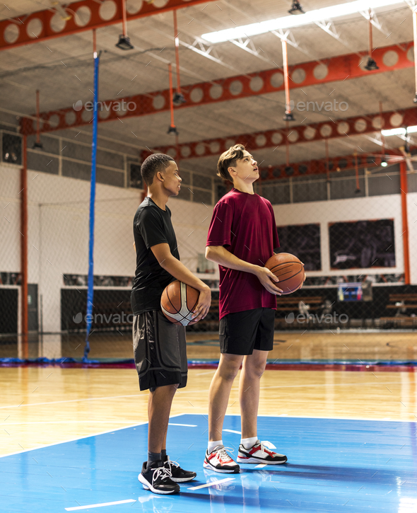 Teenage boys holding basketball on the court team and aspiration concept - Stock Photo - Images