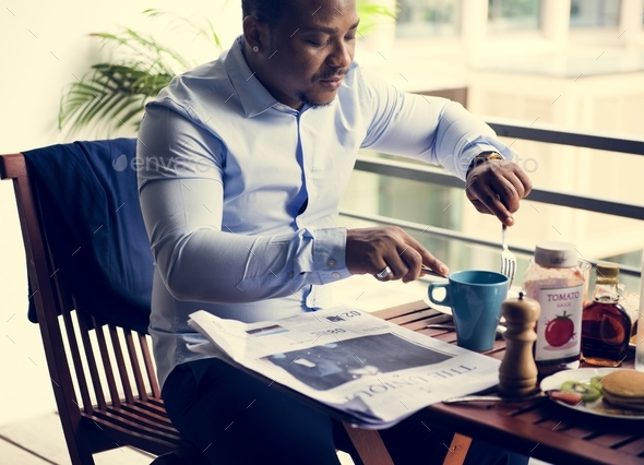 Black man sitting eating breakfast - Stock Photo - Images