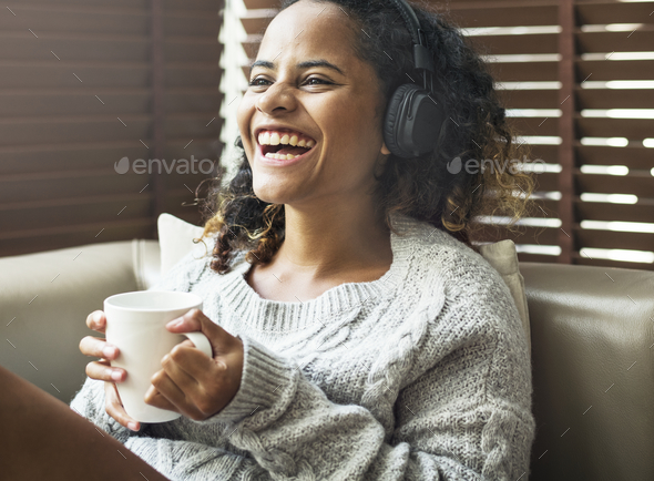 Woman enjoying music on her sofa - Stock Photo - Images