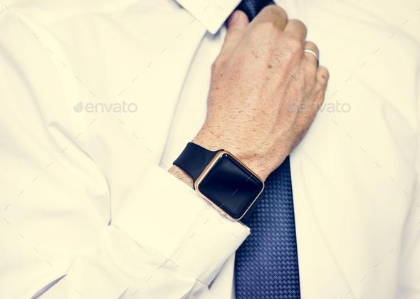 Hand with smartwatch adjust necktie - Stock Photo - Images