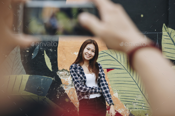 Man taking a photo of his girlfriend - Stock Photo - Images