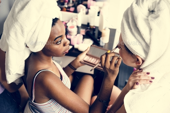 A woman applying makeup for her friends - Stock Photo - Images