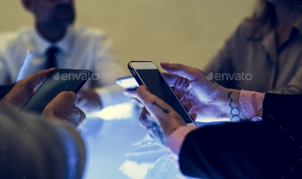 People holding smartphone in a meeting - Stock Photo - Images