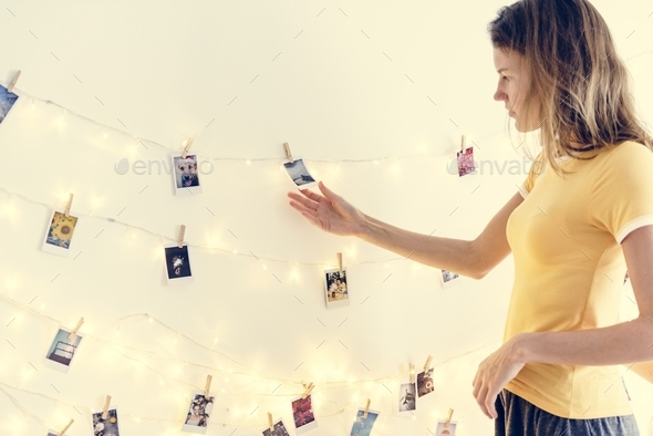 Woman looking at photos hanging with decoration lights on the white wall - Stock Photo - Images