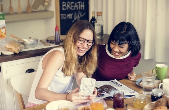 Friends looking at mobile phone while having a breakfast - Stock Photo - Images
