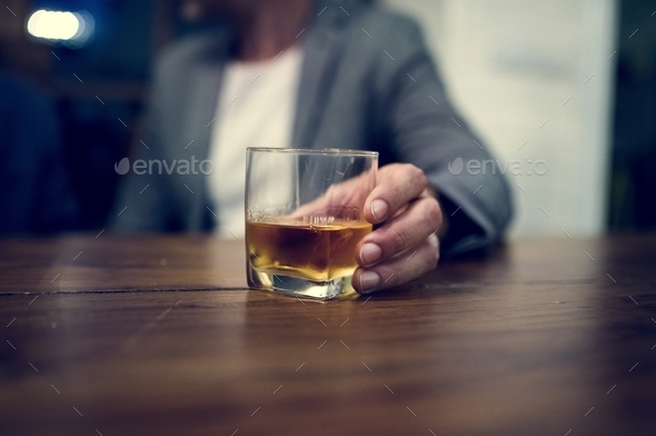 Shot of a person carrying a glass of alcohol - Stock Photo - Images