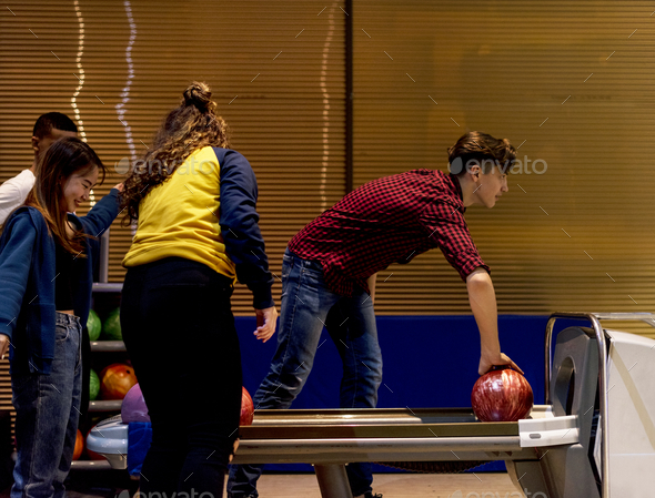 Caucasian boy picking up a bowling ball hobby and leisure concept - Stock Photo - Images