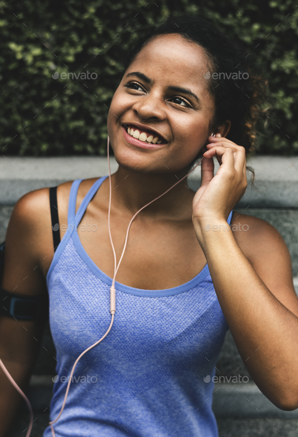 Healthy woman exercising while using technology - Stock Photo - Images