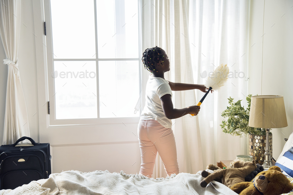 Young teen girl cleaning up the bedroom - Stock Photo - Images