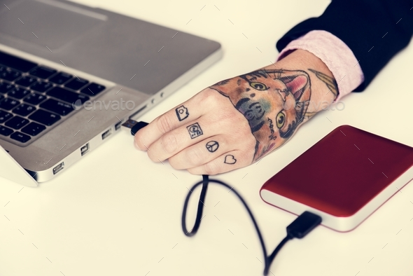 Hand with tattoo connect a external Hdd cable to laptop - Stock Photo - Images