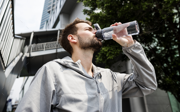 Man drinking out of a water bottle - Stock Photo - Images