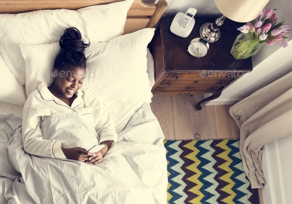 Smiling African American woman on bed using a cellphone - Stock Photo - Images