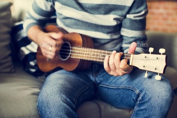 Caucasian man practicing ukulele - Stock Photo - Images