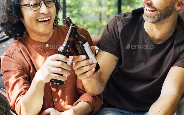 Diverse friends drinking beers together - Stock Photo - Images