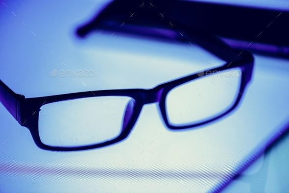 Eyeglasses on a digital desk - Stock Photo - Images