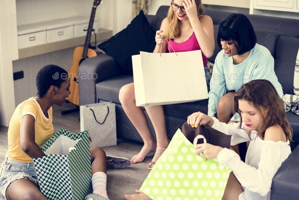 Women showing friends shopping items - Stock Photo - Images