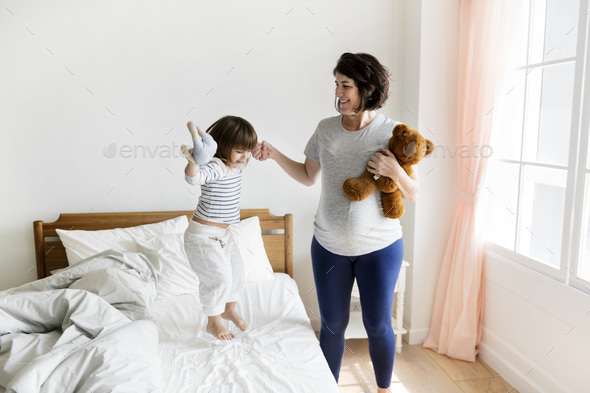 Pregnant mom spending time together with her daughter - Stock Photo - Images