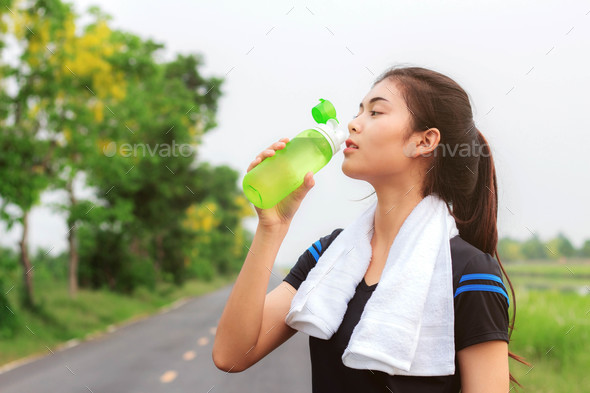 Girl drinking water after exercising - Stock Photo - Images