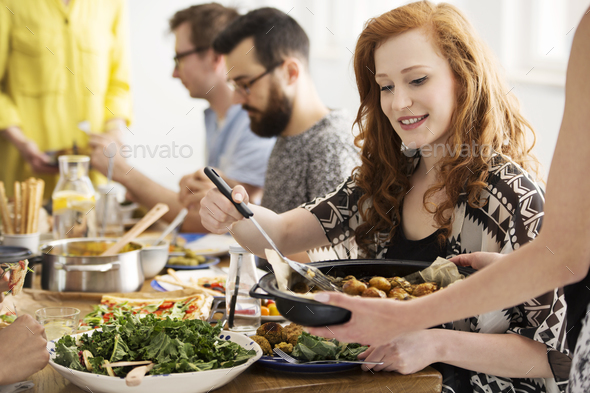 Smiling woman eating baked potatoes - Stock Photo - Images