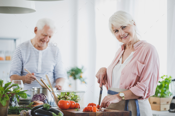 Smiling senior woman cutting tomatoes - Stock Photo - Images