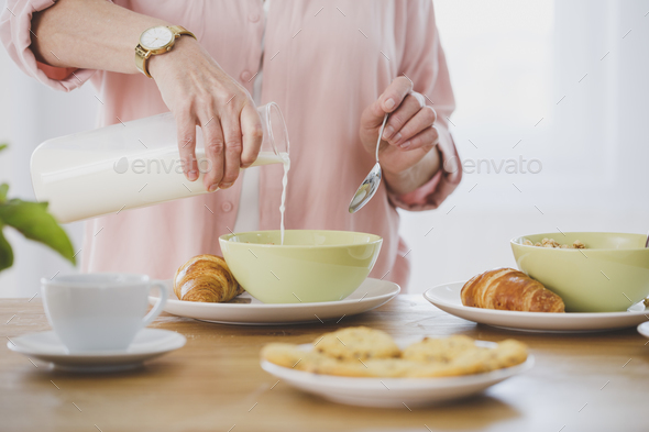 Person pouring milk into bowl - Stock Photo - Images