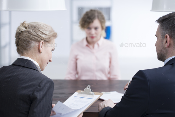 Headhunters looking at candidate references - Stock Photo - Images