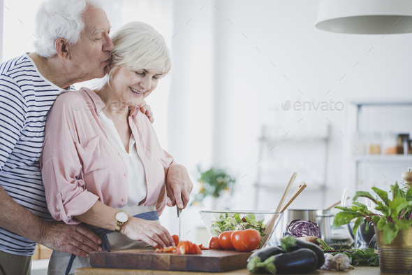 Elderly man kissing wife - Stock Photo - Images
