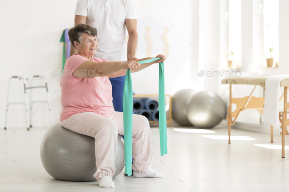 Elderly woman sitting on ball - Stock Photo - Images