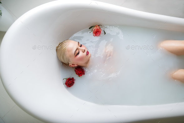 portrait of sexy girl in a bath with milk - Stock Photo - Images