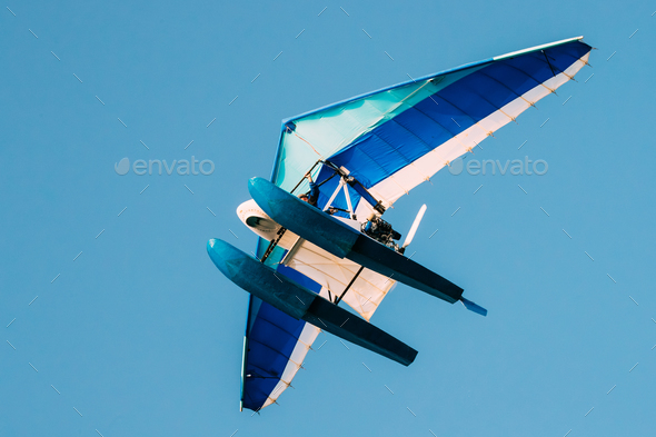 Motorized Hang Glider Flying On Blue Clear Sunny Sky Background - Stock Photo - Images