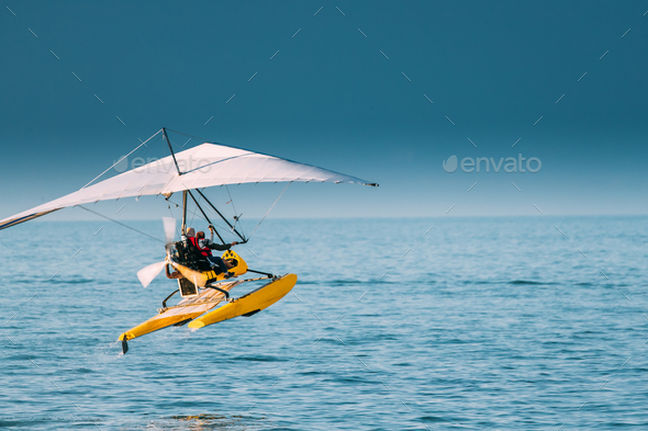 Motorized Hang Glider With Muslim Woman Take Off Frow Sea In Sun - Stock Photo - Images