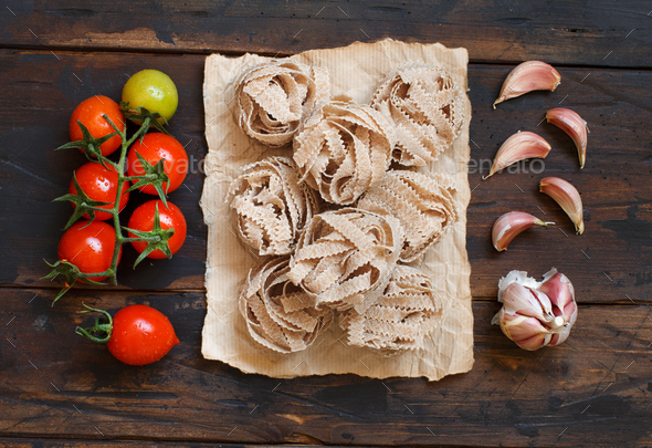 Whole wheat pasta tagliatelle, tomatoes and garlic - Stock Photo - Images