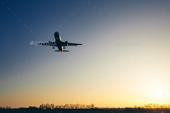 Airplane landing at golden sunset - Stock Photo - Images