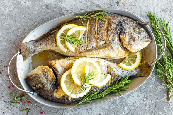 Baked fish dorado. Sea bream or dorada fish grilled - Stock Photo - Images
