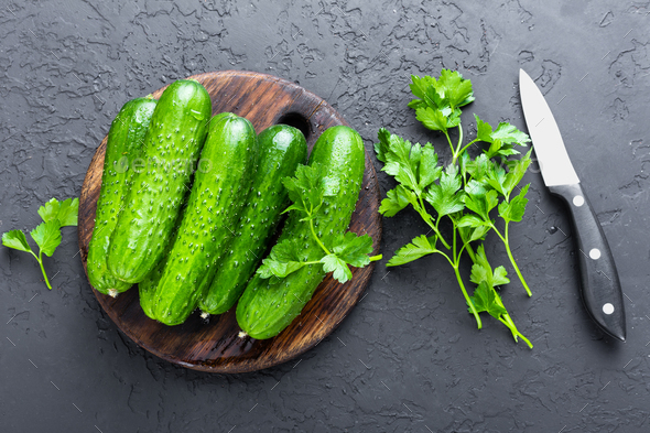 Cucumbers. Fresh cucumbers on wooden board - Stock Photo - Images